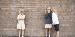 Bullying and whispering school kids in uniform